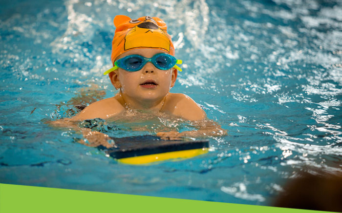 Child swimming with float, goggles and lion cap