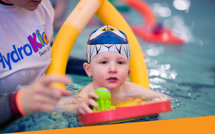 Child learning to swim with swim cap and floats