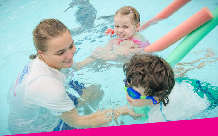 Swim teacher with boy and girl, learning with noodles